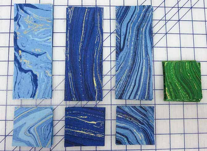 Blue Sandscapes strips and blue and green squares cut for the pieced blocks in the border