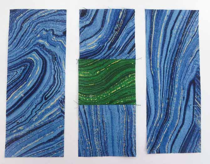 "Sew a 2½"" green square to 2 – 2½"" blue squares. Press seams toward blue."