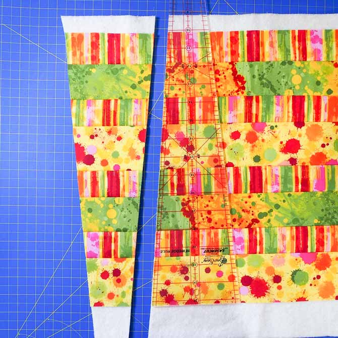wedge ruler sitting on quilted fabric sandwich and one diagonal cut made