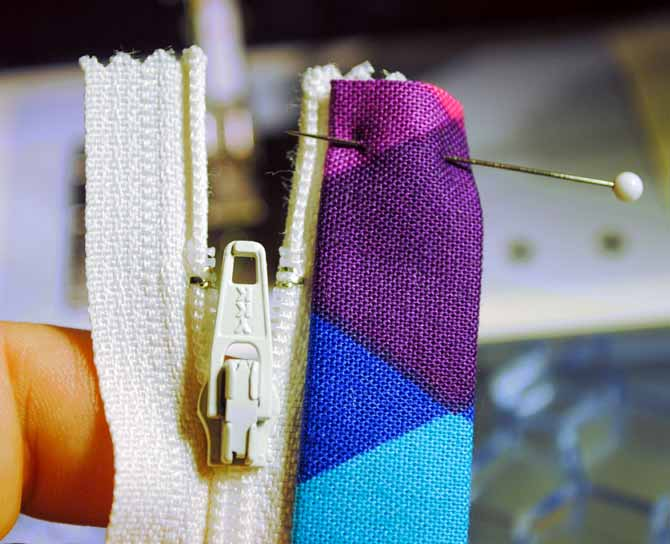 Slide one of the covers onto the edge of the zipper and topstitch