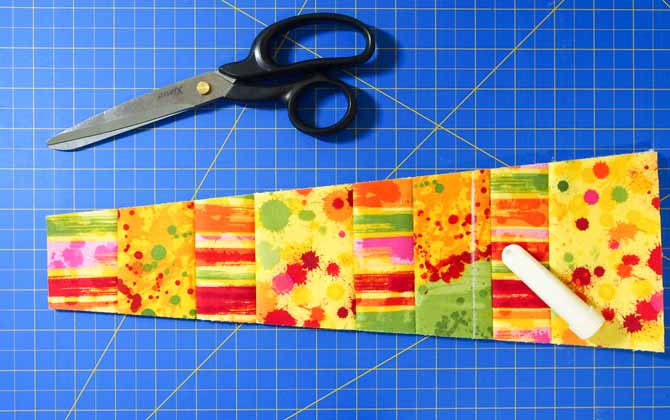 a pair of black handled scissors and multi colored fabric wedge on a blue cutting mat