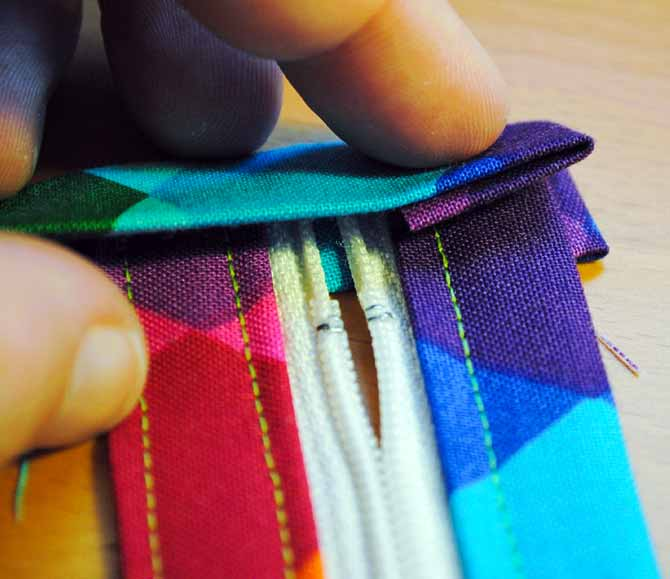 Slide the end of the zipper into the folded fabric strip and tuck in the ends