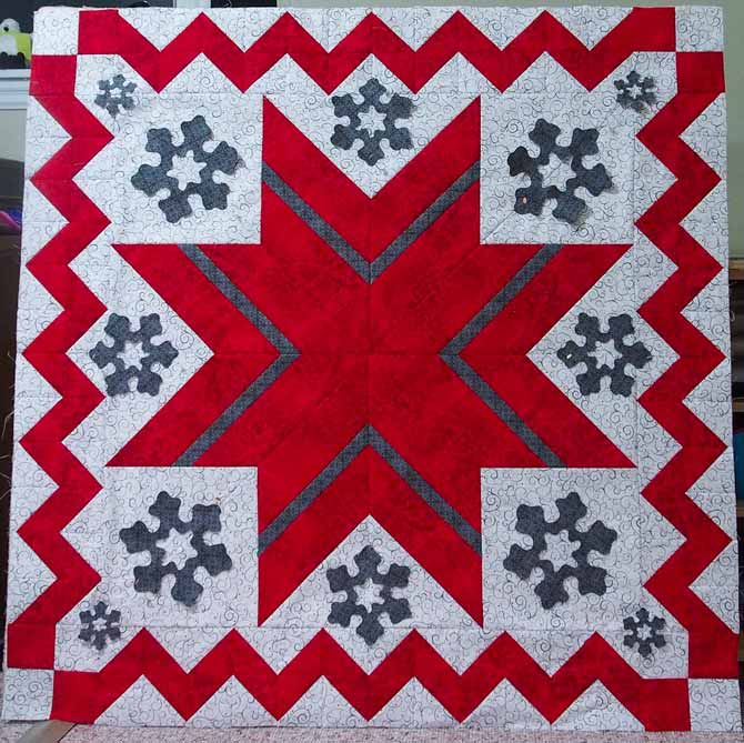 Snowflakes pinned in position on the quilt top