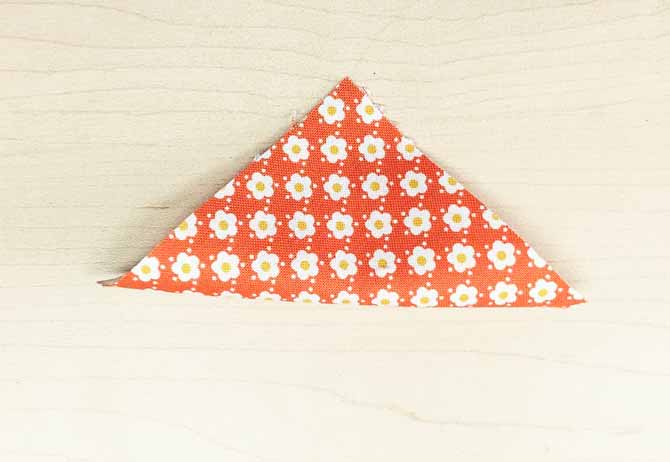 Fabric square folded along diagonal to create a triangle.