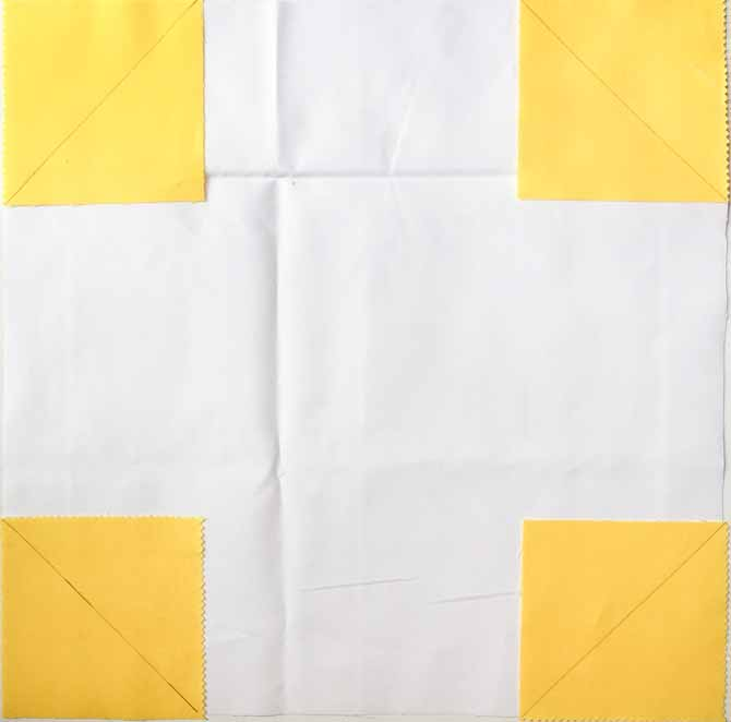 White square piece of fabric with small yellow fabric squares in each corner.