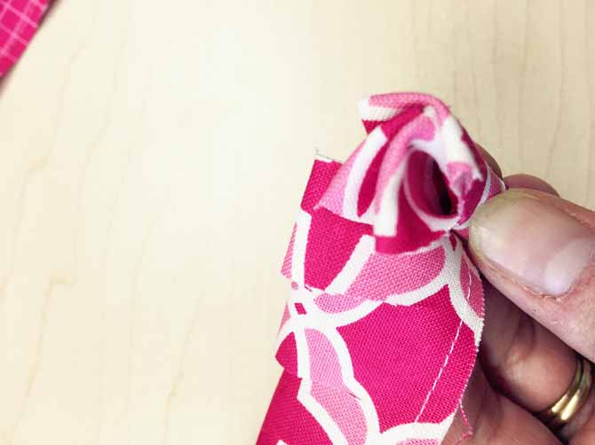 Roll up the strip tightly and make stitches every half a roll along the bottom to hold in place.