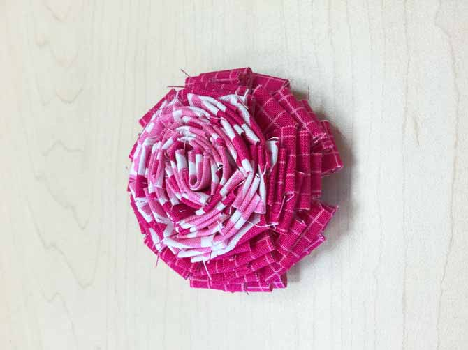 Fabric flower created by using strips of fabric.