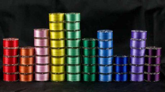 Ten stacks of WonderFil DecoBob Prewound Bobbins in multiple colors.