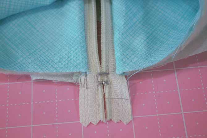 Stitch across the end of the zipper with a straight stitch or a zigzag and then trim even with the side of the bag.