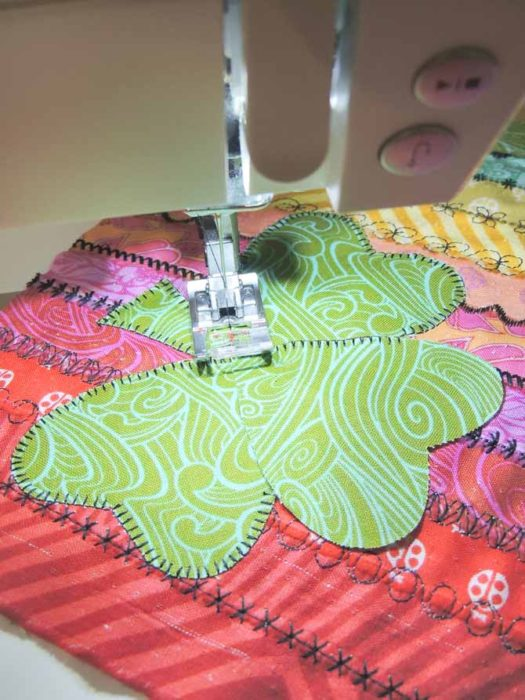 The machine blanket stitch on the passport 3.0 is used to applique the shamrock to the stitch sampler.