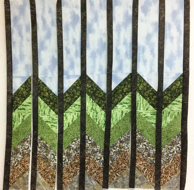 Vertical rows of a quilt top with black sashing sewn to rows - Northocott Naturescapes fabrics