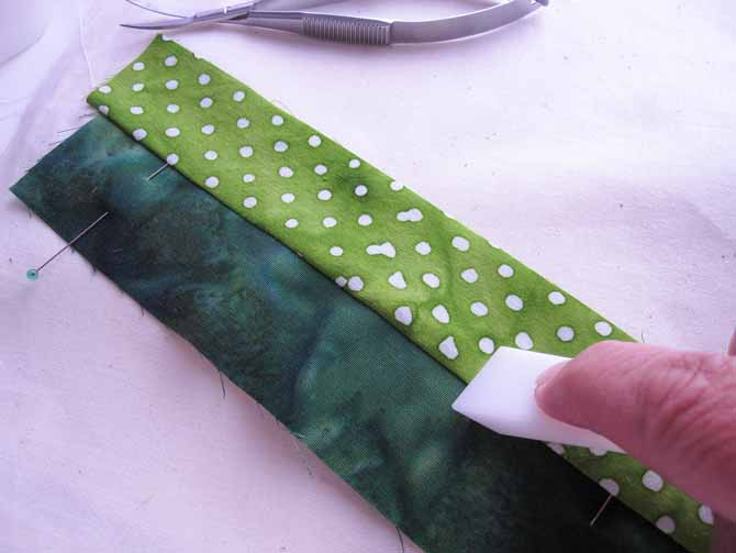 finger pressing the second strip to make the leaves