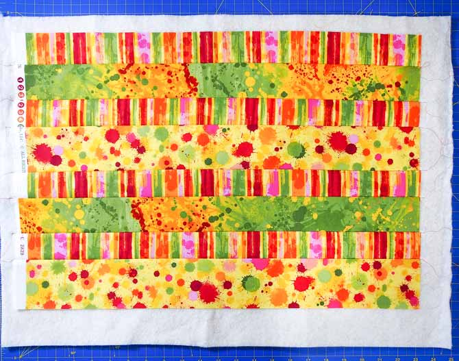 8 strips of yellow/orange/red/green fabric sewn together to make one big piece