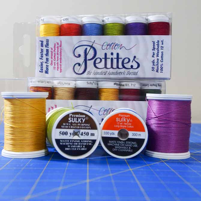 assortment of spools of Sulky thread in various colors and weights on a blue mat