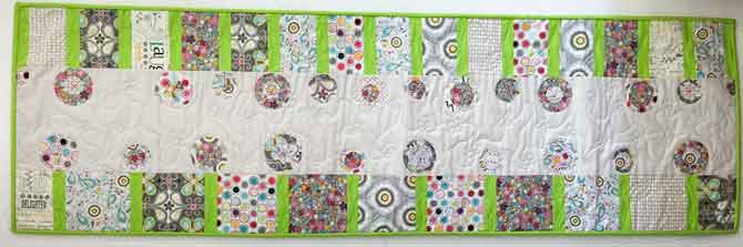 Fused flower circle table runner with pieced border.