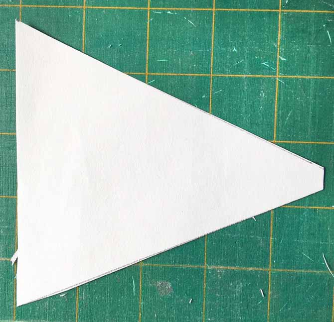 Triangular piece of paper with one corner cut off laying on an Olfa cutting mat.