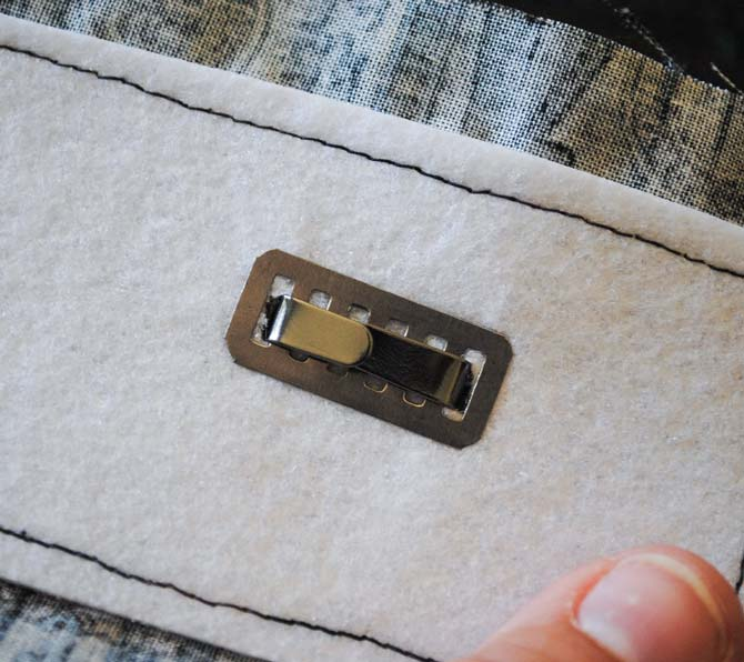 The prongs are folded to the back of the turn clasp with the reinforcement metal underneath.
