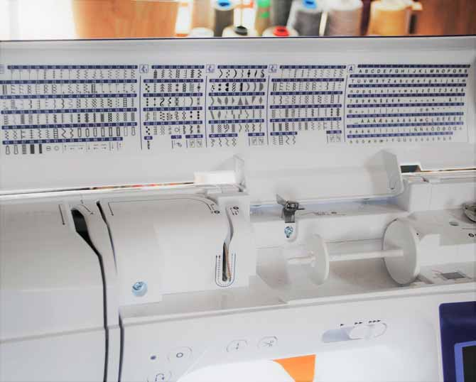 The open top cover of the Brother NQ900 showing the stitch selection chart.