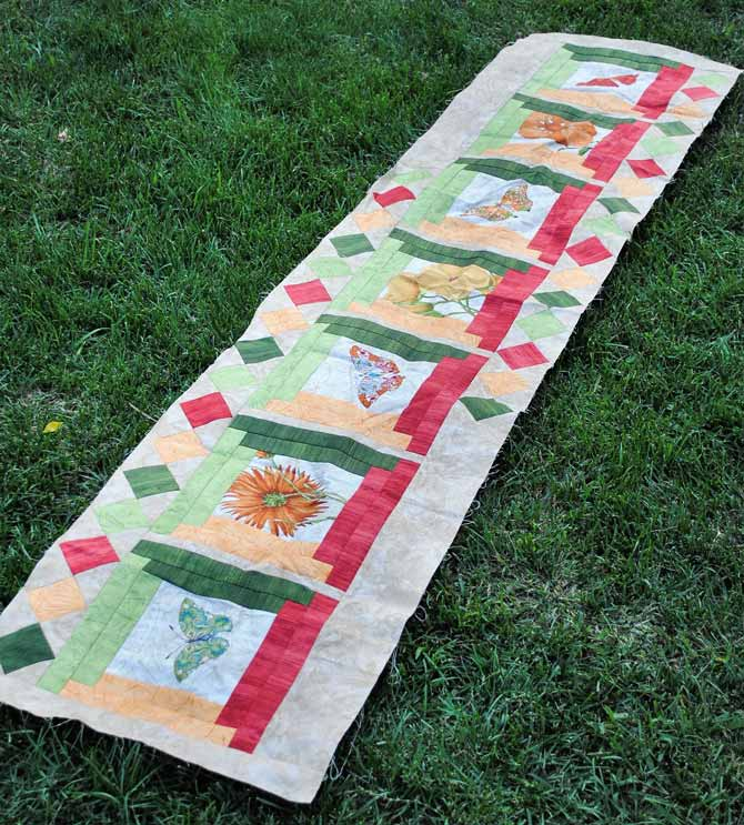 Here is the finished top for the bed runner stretched out on the lawn