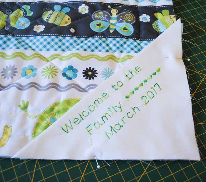 The label is pinned to the back corner of the quilt before the binding is attached with the Brother NQ900.