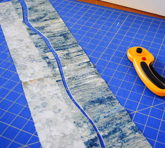 The first wavy cut through the two overlapping fabric strips