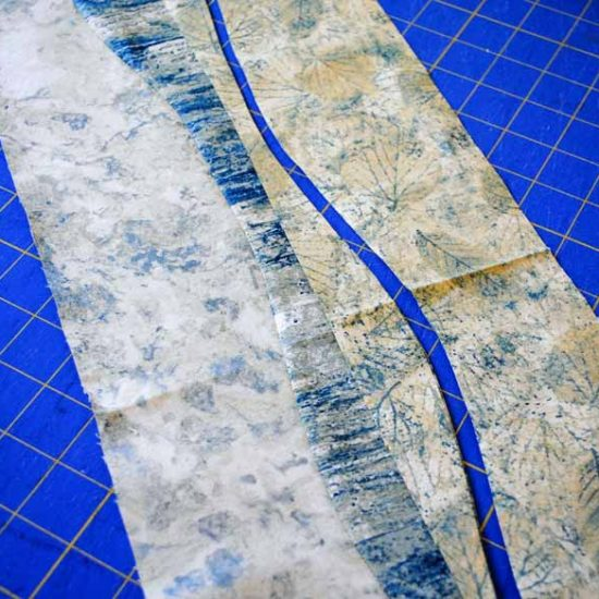 The third piece is layered on top with right side up and a second wave freehand cut is made