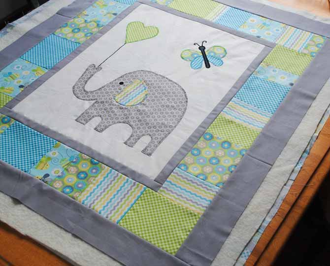 The top of the baby quilt is layered with batting and backing in preparation for quilting with the Brother NQ900.