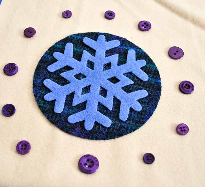 The wool applique shapes and buttons are arranged on the background