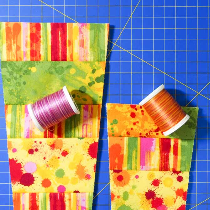 2 wedges of differing heights with a spool of pink and a spool of orange thread