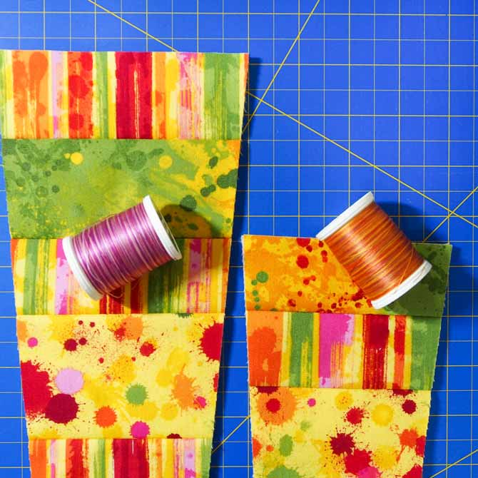 front and back pieces of holder in multicolored fabric with 2 spools of thread