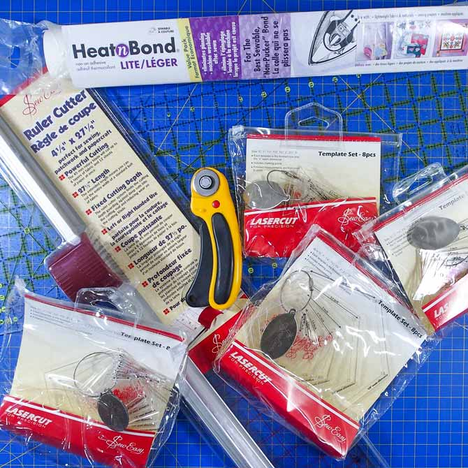 A variety of quilting tools and templates lying on a blue cutting mat