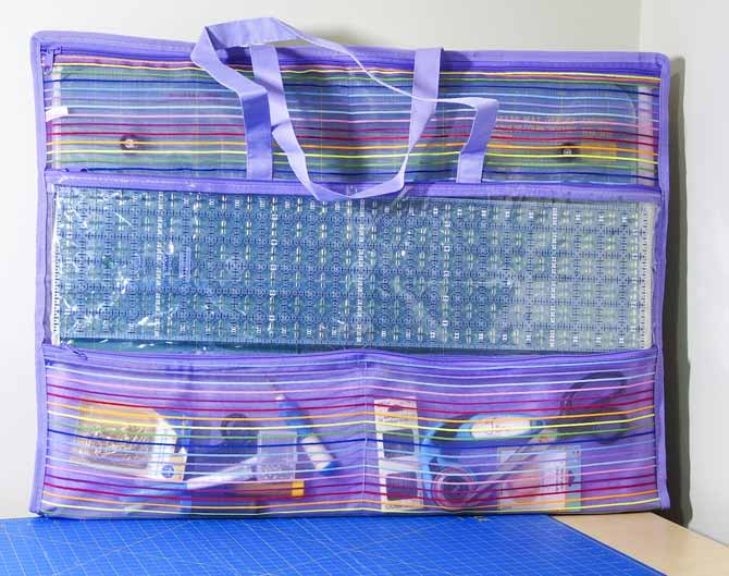 Purple and striped mesh bag with handles filled with quilting tools sitting on a blue Unique mat