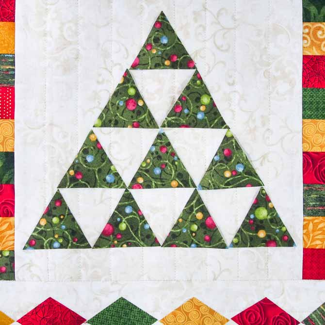 A tree made with green triangles on cream fabric