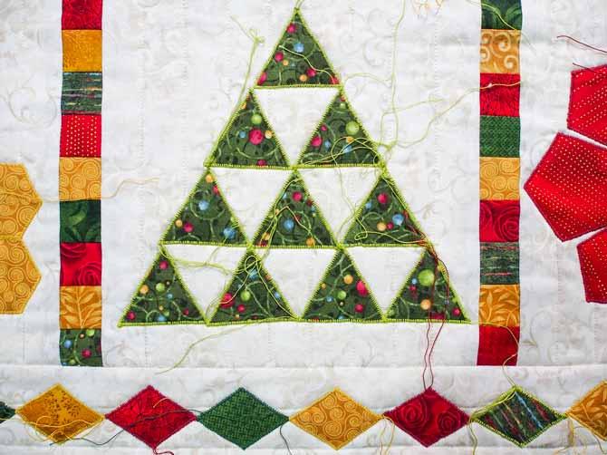 Bright green thread stitched around green triangles on cream background