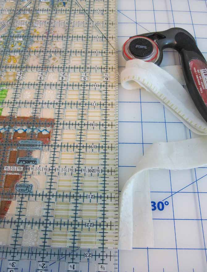 A quilter's ruler and rotary cutter set on a cutting board to trim the studio bird mini quilt. WonderFil Specialty Threads.