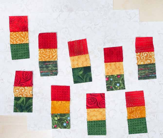 Sets of green/red/gold squares on a cream background to be used to make the sashing