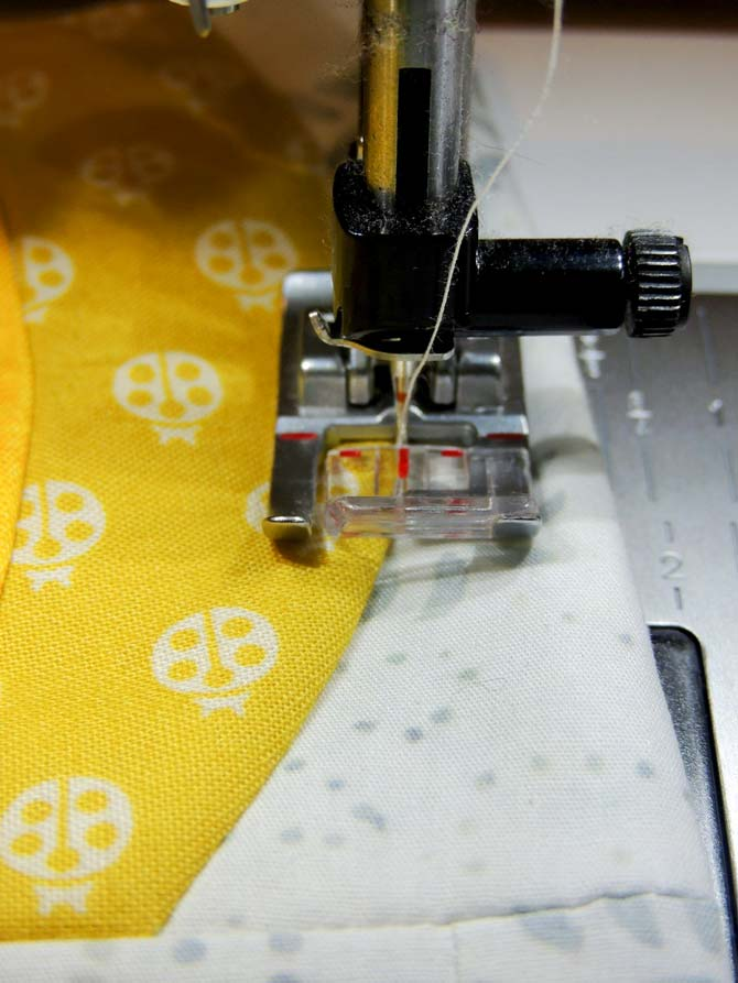Using presser foot 1A to stitch in the ditch on the quilted pineapple pocket.