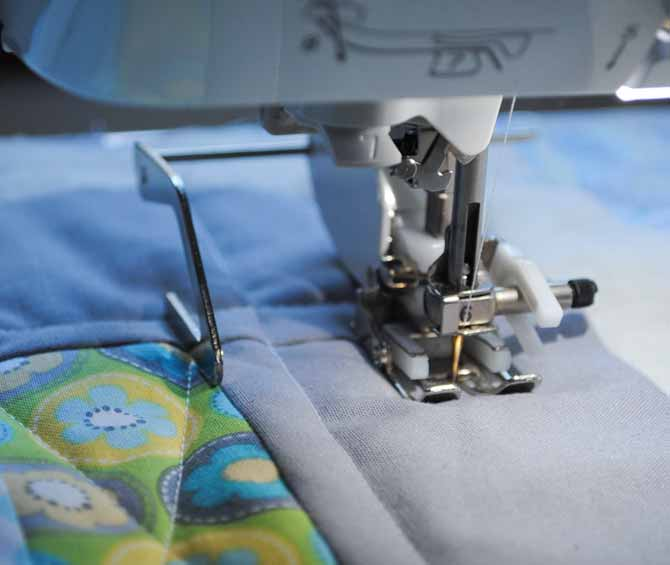 The quilting guide on the Brother NQ900 walking foot is used to quilt straight lines on the outer border of the baby quilt.