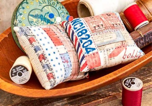 2 pin cushions, pins in a basket with spools of Coats & Clark thread