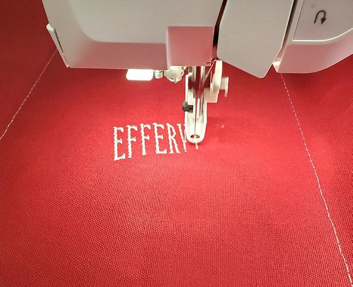 Stitching out white letters on a red canvas with the Husqvarna Viking Designer Brilliance 80