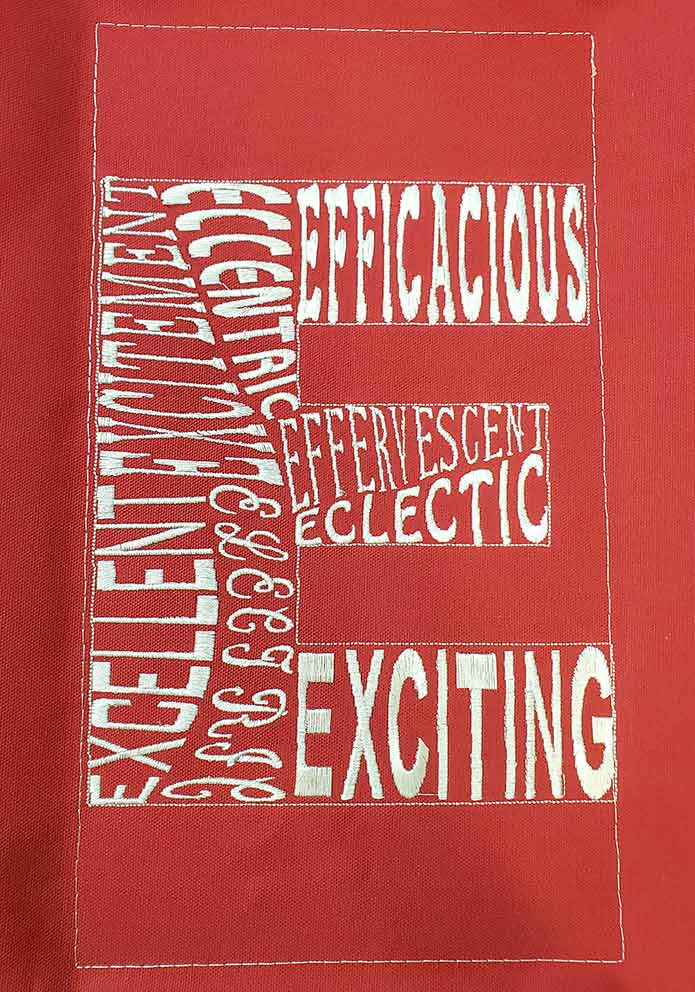 An embroidered letter E created in PREMIER +2 Embroidery System and stitched out in a white thread on red canvas