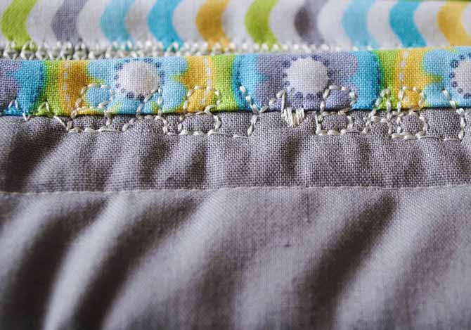 "The word ""Baby"" is stitched repeatedly on the binding of the baby quilt made with the Brother NQ900 sewing machine."