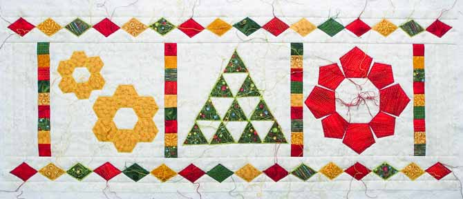 Zigzag stitching done in red, green and gold around each shape in the corresponding color